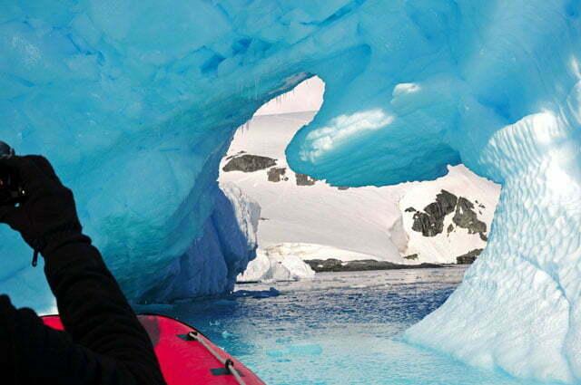 De bote entrando no túnel formado pelo iceberg