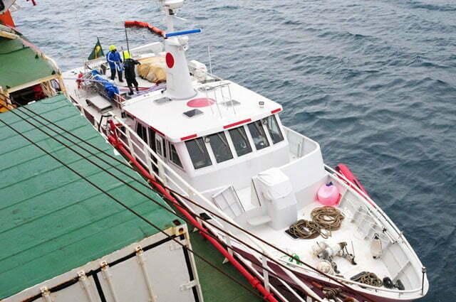 Barreira de contenção cerca o barco na faina de abastecimento
