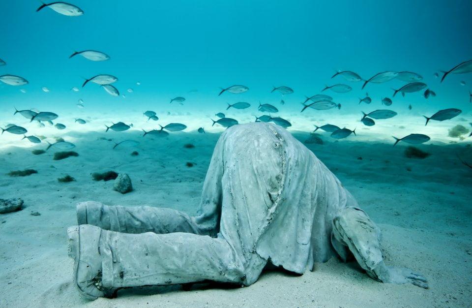 imagem escultura subaquática homem cabeça na areia
