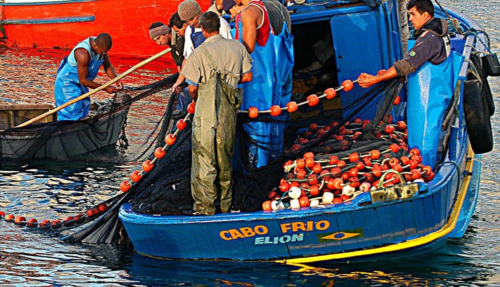 Eventos extremos, peso para a economia, imagem de pescadores artesanais com rede