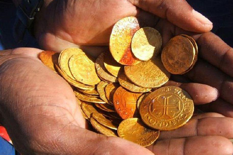 Tesouro encontrado em naufrágio, imagem de uma mão segurando moedas de ouro antigas