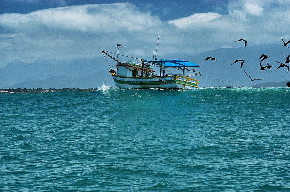 Fiscalização no litoral, imagem de barco de pesca arrastando-na zona de-arrebentacao