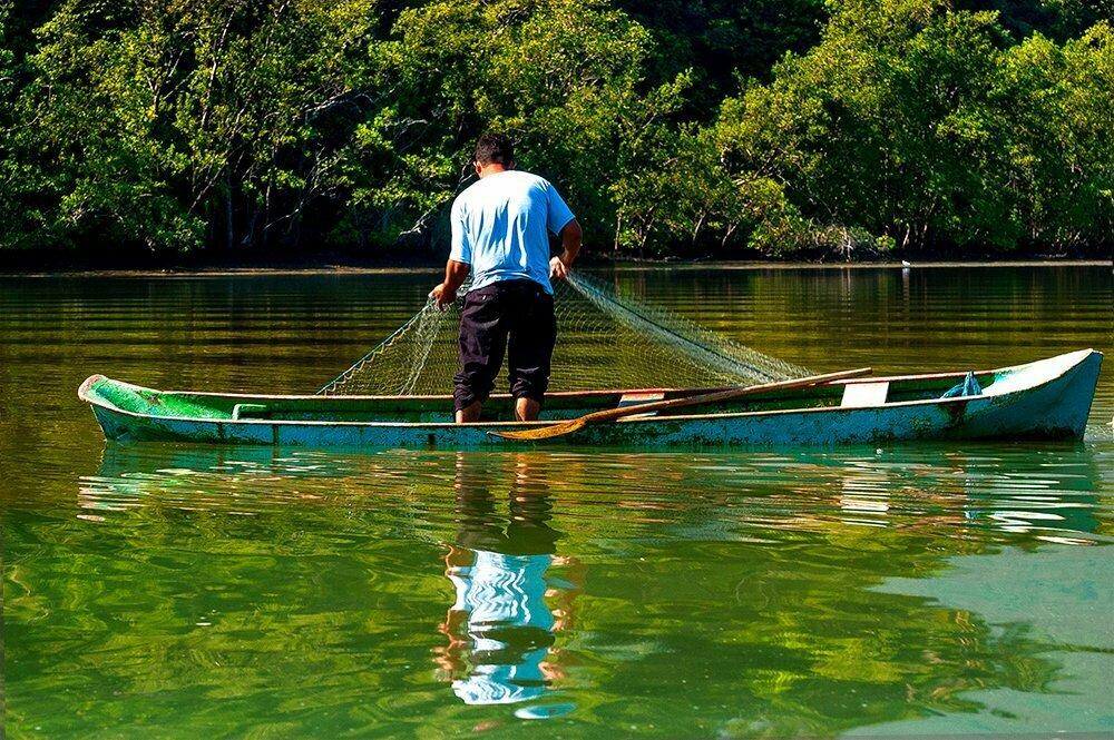Viagens do Mar Sem Fim em fotos, imagem de pescador com rede em canoa