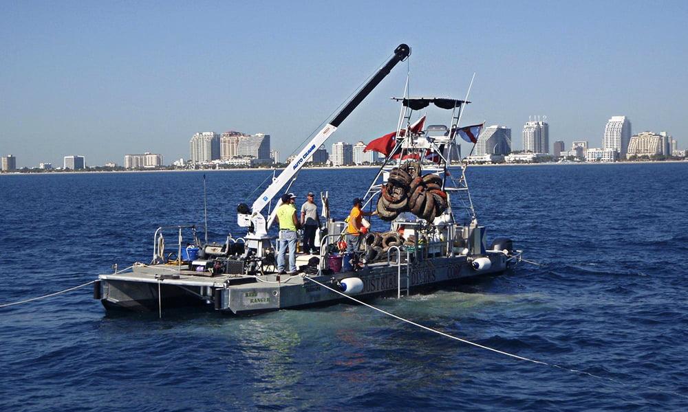 Recifes artificias com pneus, imagem de barca retirando pneus do mar da Flórida
