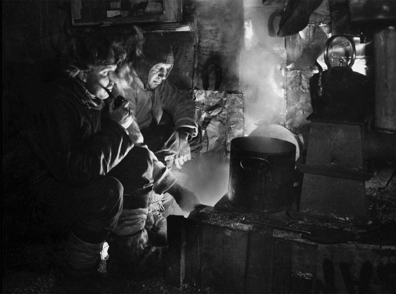 imagem de membros da expedição Terra Nova costurando agasalhos