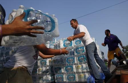 Lago tem água totalmente verde, imagem de voluntários distribuindo água
