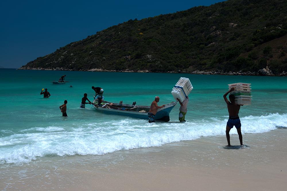 imagem de pescadores e-canoa-na praia em Arraial do Cabo