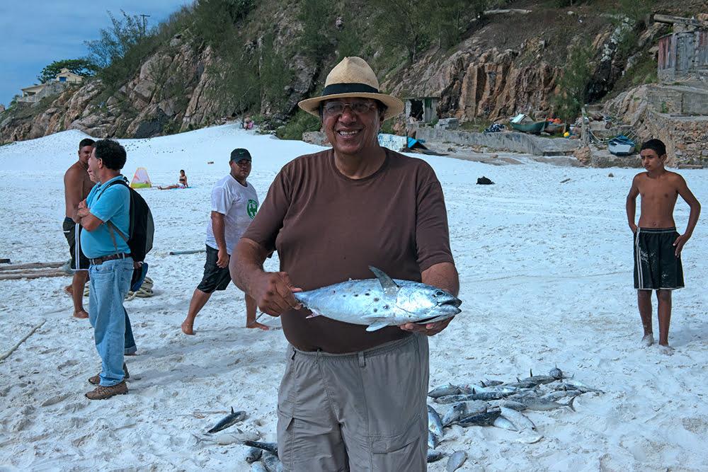 imagem de homem segurando um peixe em Arraial do Cabo