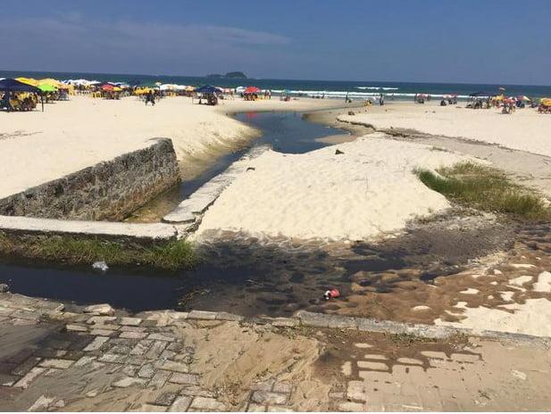 Litoral de São Paulo e saneamento, imagem de vazamento de esgoto na praia de Enseada, Guarujá