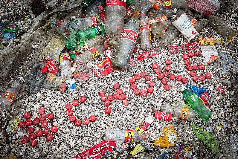 imagem de garrafas de coca- cola em praia ilustra post Coca- cola e plástico no mar