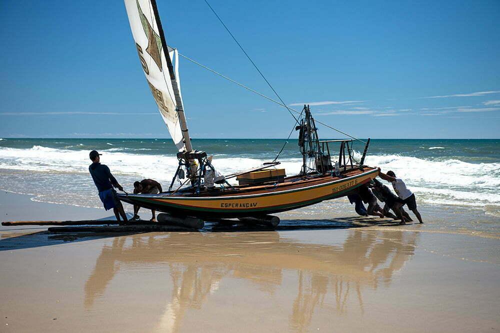 imagem de jangada sendo empurrada na praia