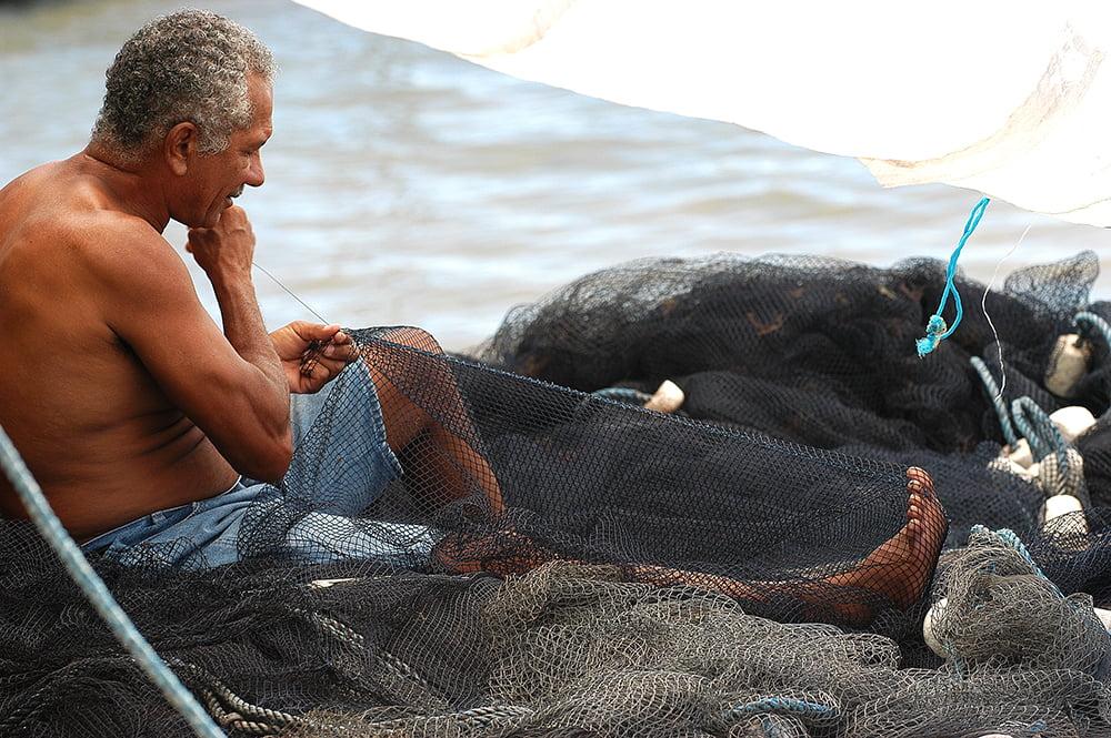imagem de pescador costurando rede em Itapissuma