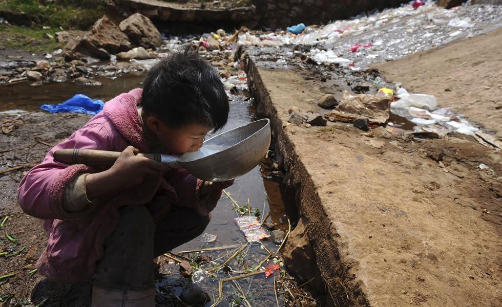 imagem de criança bebendo água em meio ao lixo