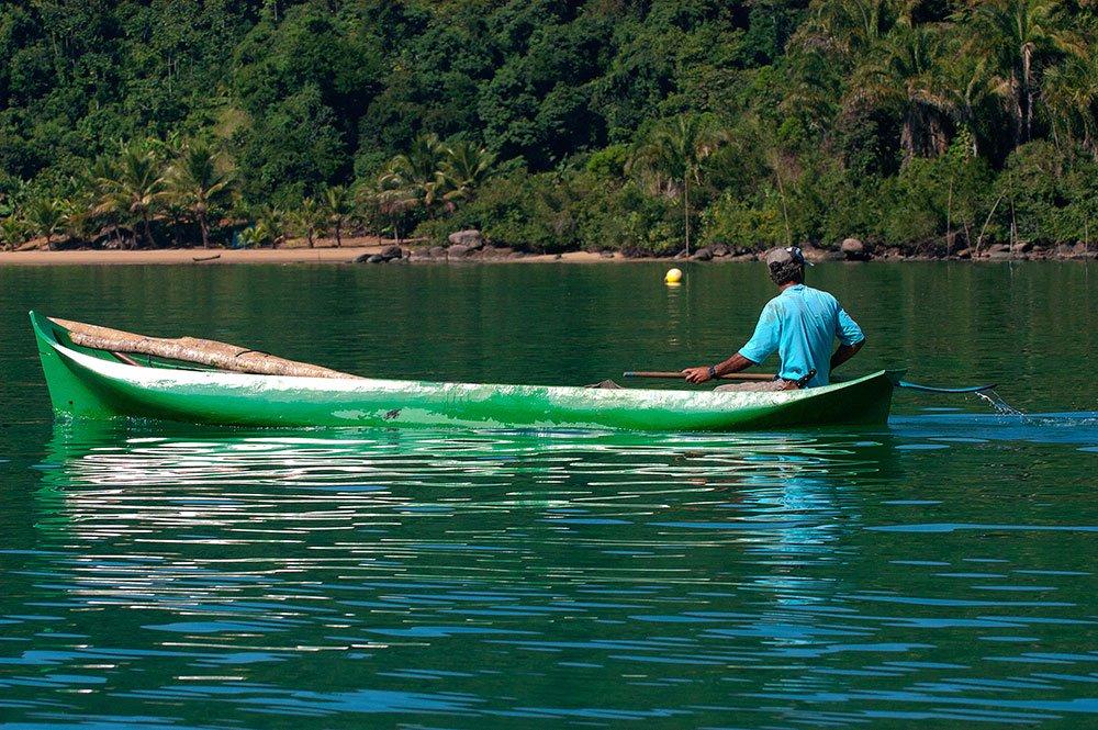 imgem de pescador em canoa no saco de mamanguá, paraty