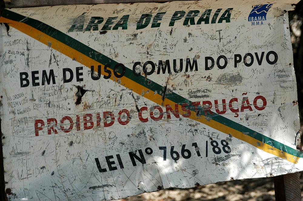imagem de placa mostrando proibido construir na praia