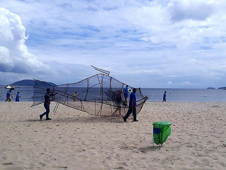 imagem de lata de lixo em forma de peixe colocada na praia
