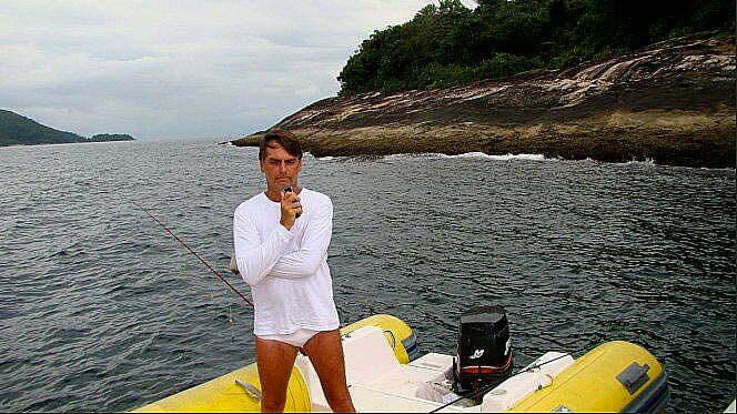 imagem de jair bolsonaro com o celular na mão, a vara de pesca apoiada no casco, na Esec de Tamoios