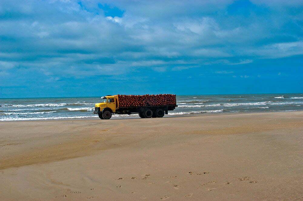 imagem de caminhão carregado na praia