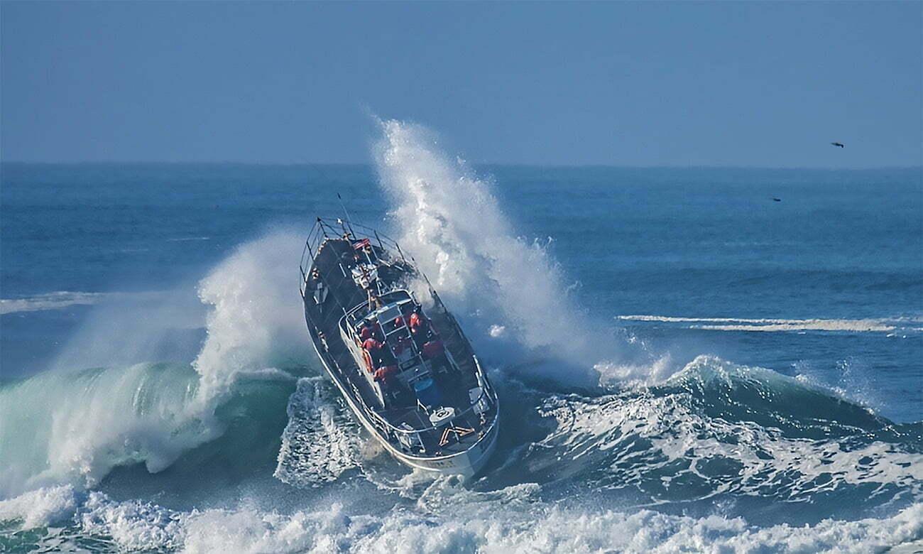 imagem de barco da guarda costeira do Oregon enfrentando onda