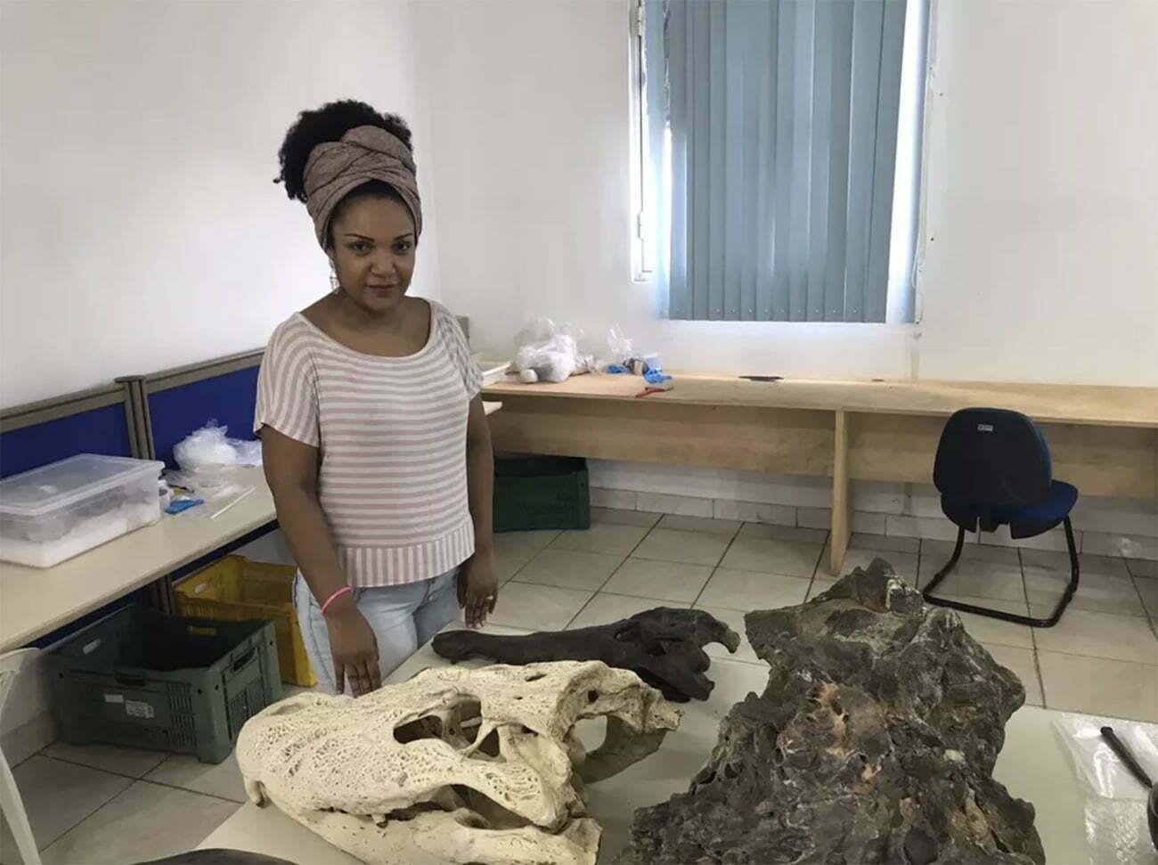 imagem de pesquisadora com fóssil de peixe-boi