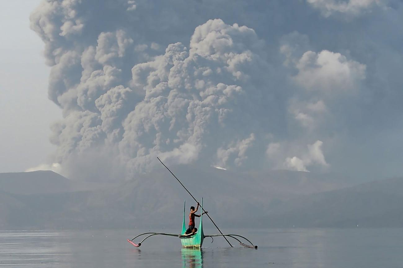 imagem de homem em canoa com vulcão ao fundo