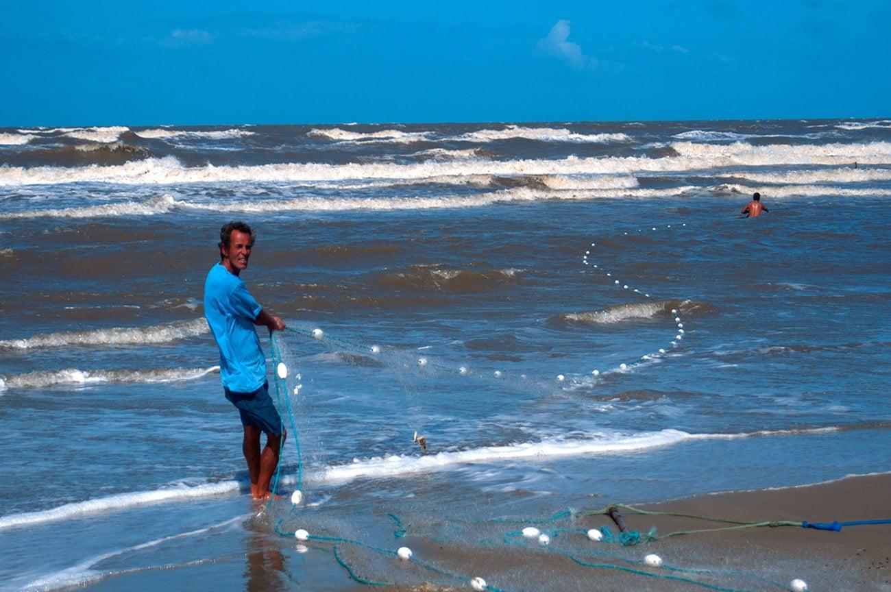 Imagem de pescador passando rede na área de arrebentação