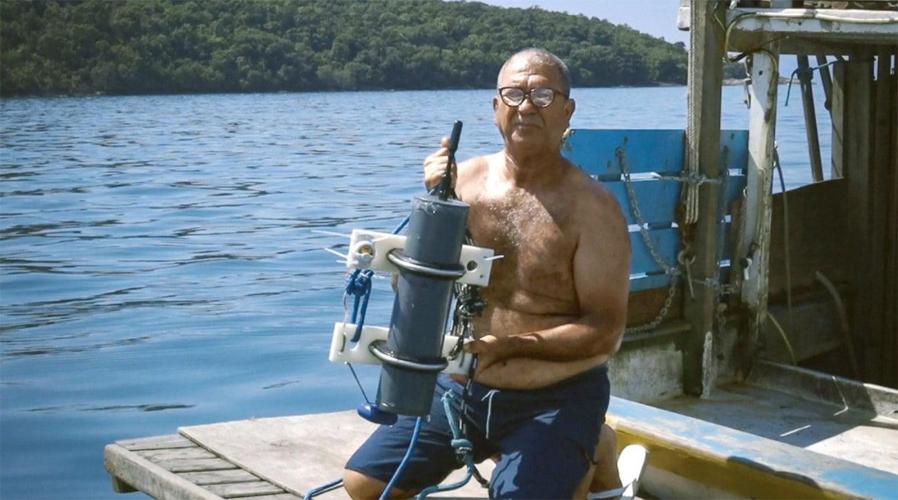 Imagem de pescador com hidrofone pesquisando as toninhas