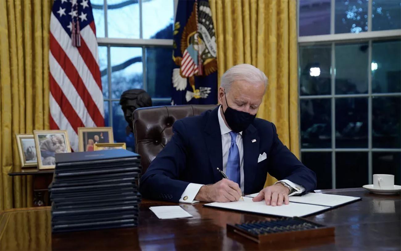 Imagem de Joe Biden assinando atos a favor do meio ambiente