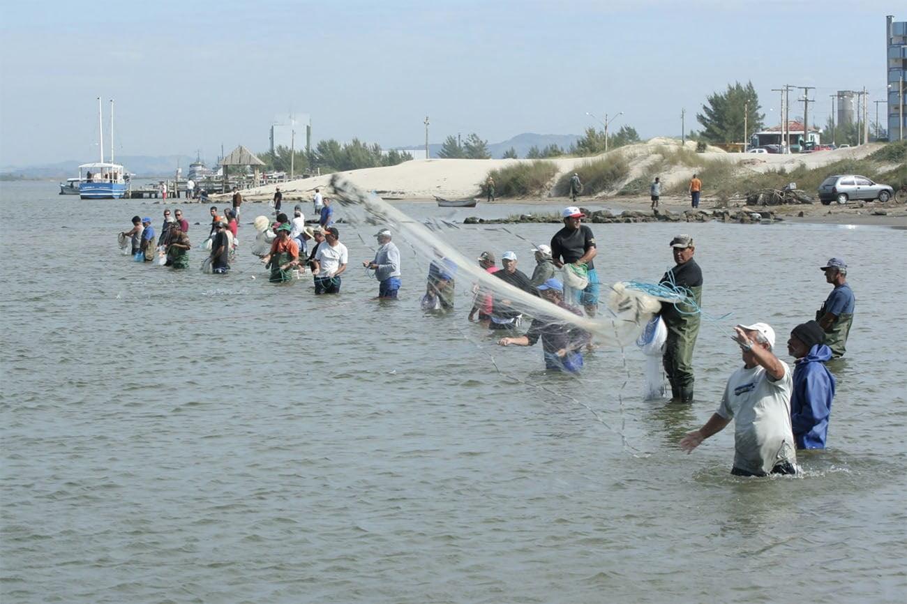 Imagem de pescadores artesanais em Laguna a espera dos botos