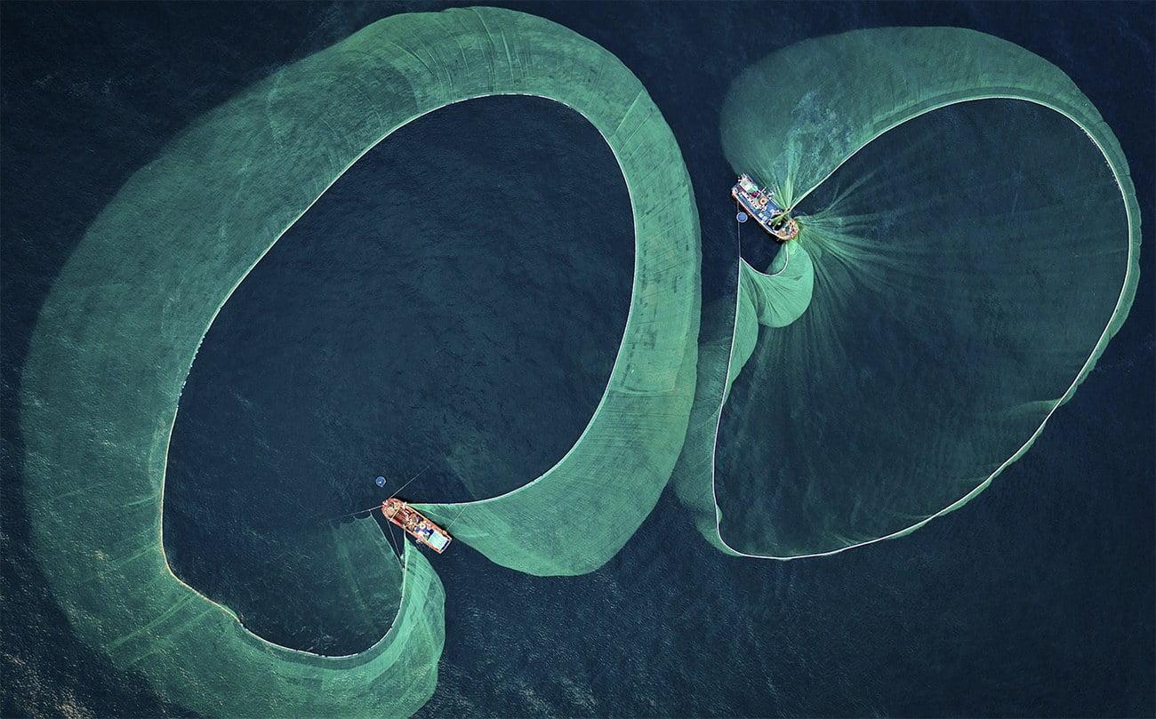 imagem aérea de barcos soltando redes de pesca